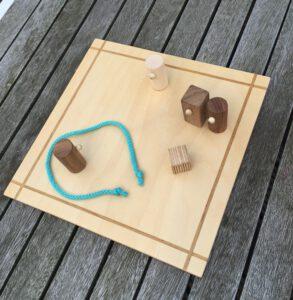 Runde und eckige Holzfiguren auf einem Holzbrett mit türkisem Band um eine Figur gelegt